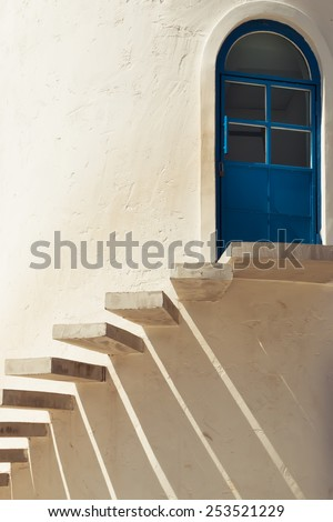stairs leading to a door in cement wall with light and shadow - stock photo