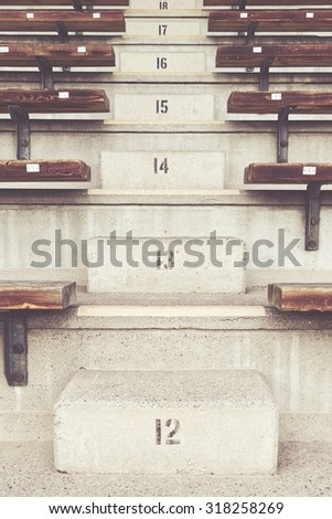 Stairs on the bleachers at an arena with numbers 12-18. Filters applied - stock photo