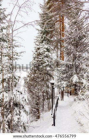 Stairs with a lantern near the house in winter covered by snow with trees around