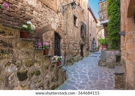 Stairs with colorful flowers in a Tuscan old town - stock photo