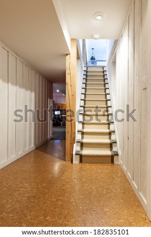 Stairway to finished basement in home interior with wood paneling and cork flooring - stock photo