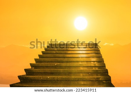 Stairway to heaven. Stairs towards sun on the orange sunset with clouds - stock photo