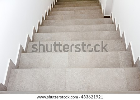 Stairway with metallic banister in a new modern building. Every building is required to have emergency stairways as safety measure. - stock photo