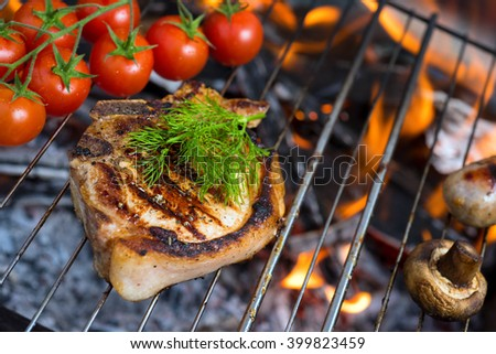 Stake grill and tomatoes with flame on background - stock photo