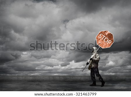 Stalker in gas mask with precaution stop signboard - stock photo