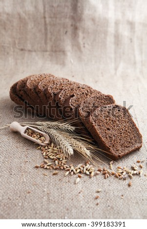 Stalks of dried whole wheat stalks and grains next to single loaf of delicious rye bread with slices on brown cloth  - stock photo