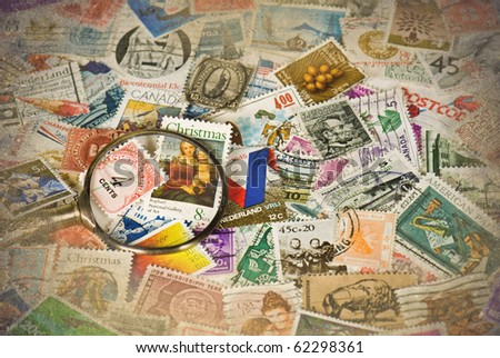 stamp collection with magnifying glass - stock photo