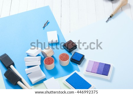 stamp ink pad, lino cutter , papers and rubbers on white wood table - stock photo