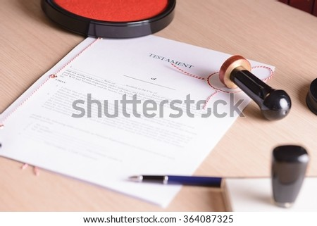 Stamp of notary public on last will. Notarial acts in the background. - stock photo