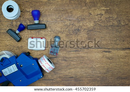 Stamp pad and price tagging gun over wooden background flat lay - stock photo