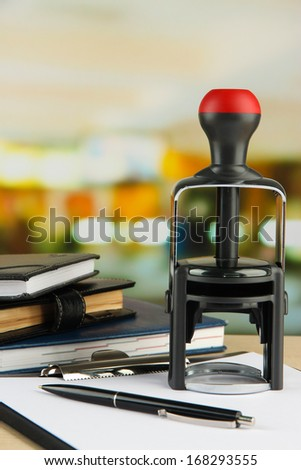 Stamp with notepads and clipboard on table on bright background - stock photo