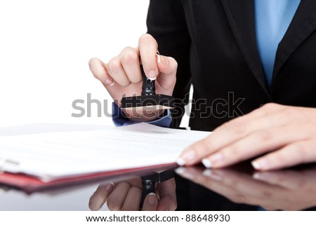 Stamping hand - Young businesswoman (or notary public) seating at the desk in office and stamping document - stock photo