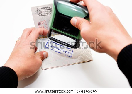 Stamping passport with blue stamp approved - stock photo