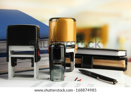 Stamps with notepads and papers on table on bright background - stock photo