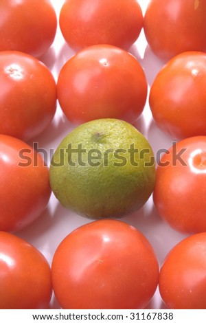 stand alone green lime amongst the tomatoes - stock photo