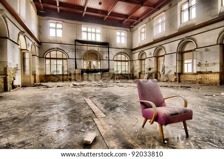 Stand-alone pink chair in abandoned dance hall - stock photo