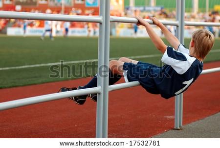 stand by boy in sport uniform in stadium - stock photo