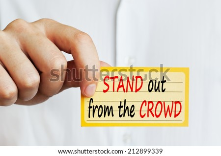 Stand out from the crowd concept. Businessman holding in his hand a card with a business message text wording on it. - stock photo
