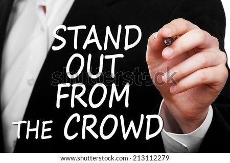 Stand out from the crowd concept. Businessman wearing black suit writing a business message text  - stock photo