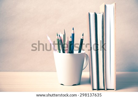 stand up book with color pencil on wood background vintage style - stock photo