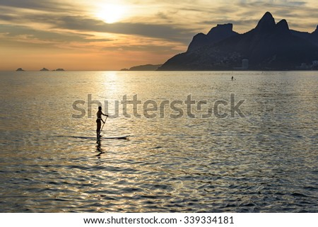 Stand up paddle at Arpoador beach in Ipanema during sunset with the hill Two Brothers and the Pedra da Gavea in the background