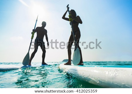 Stand up paddle board couple paddleboarding . Young caucasian couple on Thailand beach on summer holidays vacation travel. - stock photo