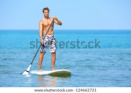 Stand up paddle board man paddleboarding on Hawaii standing happy on paddleboard on blue water. Young caucasian male model on Hawaiian beach on summer holidays vacation travel. - stock photo