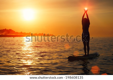 Stand up paddle board yoga performed by beautiful girl on the bright sunset background, yoga training on the beach - stock photo