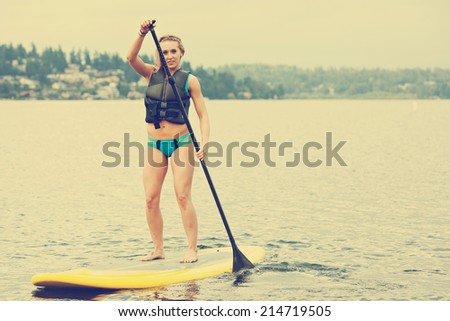 Stand up paddle boarder, filtered image - stock photo