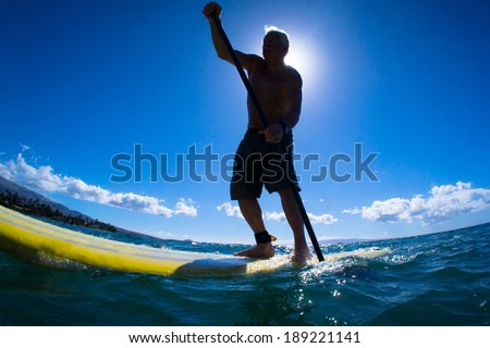 Stand up paddle boarder paddling off the coast of Maui, Hawaii  - stock photo