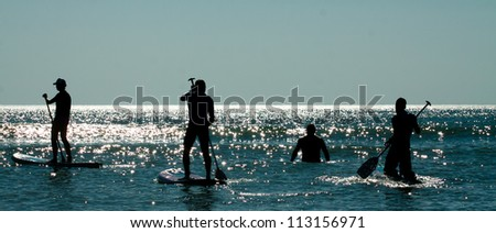 stand up paddle group on the water - stock photo