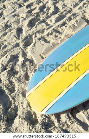 Stand up paddle long board surfboard in bright blue and yellow on Copacabana Beach Rio de Janeiro - stock photo