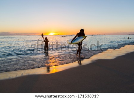 Stand Up Paddle rider and a surfboard rider walking in the sunset of Waikiki Beach on Oahu, Hawaii, - stock photo