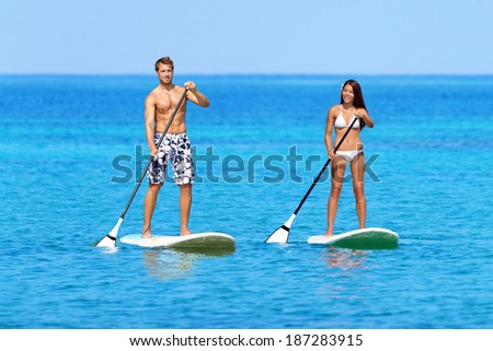 Stand up paddleboarding beach people on stand up paddle board, SUP surfboard surfing in ocean sea on Big Island, Hawaii Beautiful young mixed race Asian woman and Caucasian man doing water sport. - stock photo