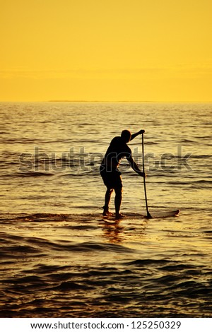 Stand up paddler at sunset, paddle board sport.  - stock photo