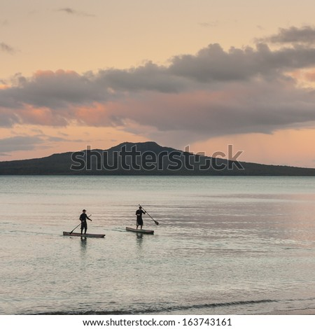 stand up surfers and Rangitoto Island at sunset - stock photo
