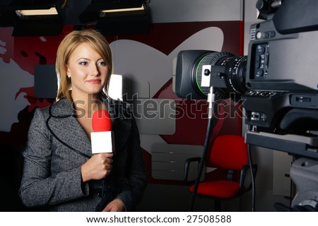 stand up transmission with serious smiling journalist woman in front of the video camera - stock photo