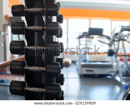 Stand with a dumbbell in the gym