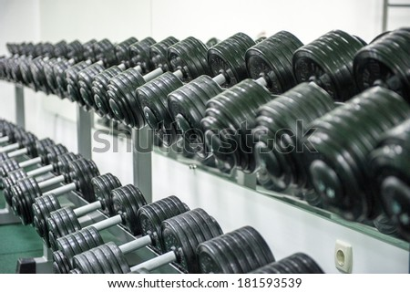 stand with dumbbells in the gym