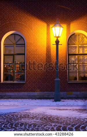 Standalone Lamp and brick wall in twilight - stock photo