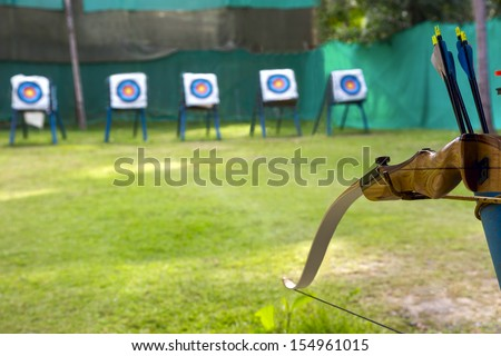Standard colorful target for archery. Sporting a bow and arrows in the foreground - stock photo