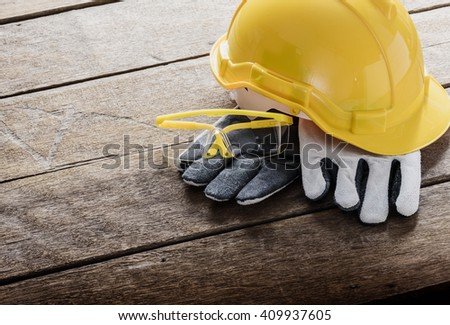 Standard construction safety equipment on wooden table and Light from the window - stock photo