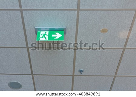 Standard international symbol safe exit sign is hanging from the ceiling. EXIT sign, echo of steps in a large hall. Emergency green international exit sign is in a public building. - stock photo