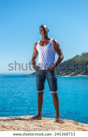 Standing African black man wearing white vest and blue short jeans. Male model thinking while isolated alone by a blue ocean and sky background. Cape Town South Africa - stock photo