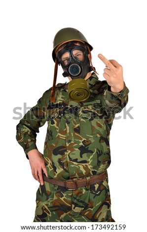 Standing Army Soldier with Green Helmet And Gas Mask Giving the middle finger - stock photo