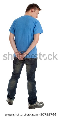 standing back young man with handcuffed hands - stock photo
