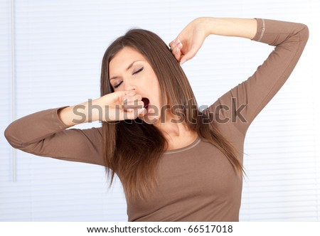 standing beautiful woman in brown blouse, yawning and stretching - stock photo