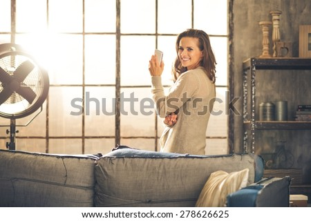 Standing behind a sofa, looking over her shoulder, a brunette woman is holding her phone and smiling. Industrial chic ambiance and cozy atmosphere, sunlight is streaming through the loft window. - stock photo