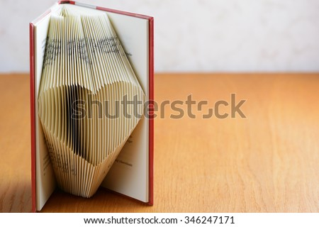 Standing book with folded pages to form a lovely heart. Book folding is an art form that is growing very popular in the crafting community. Copy space to right. - stock photo