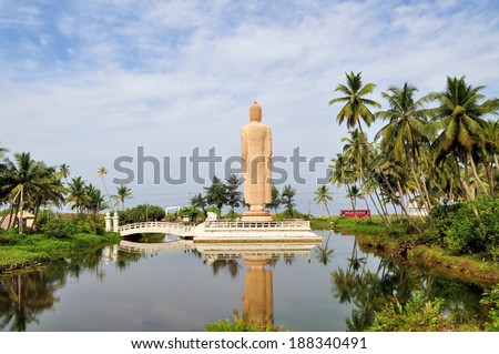 Standing Buddha at the sea with reflection - stock photo